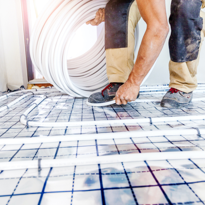 Tradesperson laying underfloor heating pipes