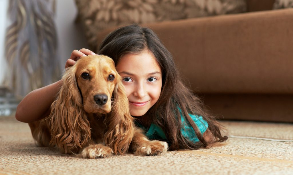 Girl and dog lying on carpet